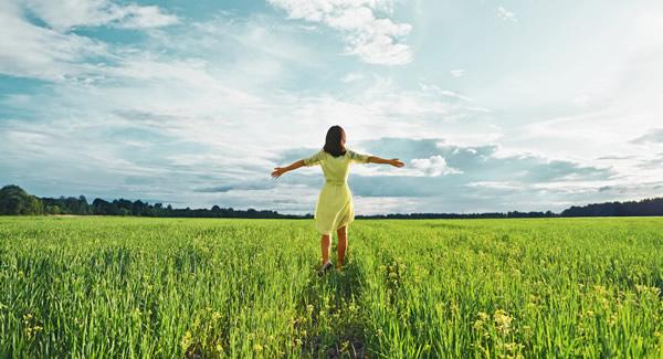Body Love Coaching - happy woman walking in grassy field