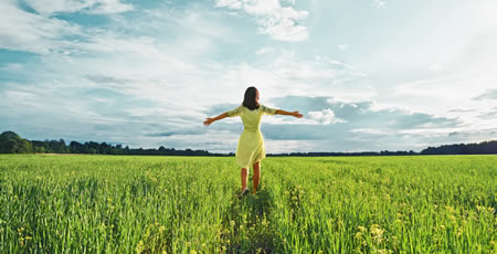 Body Love Coaching - happy woman walking in grassy field
