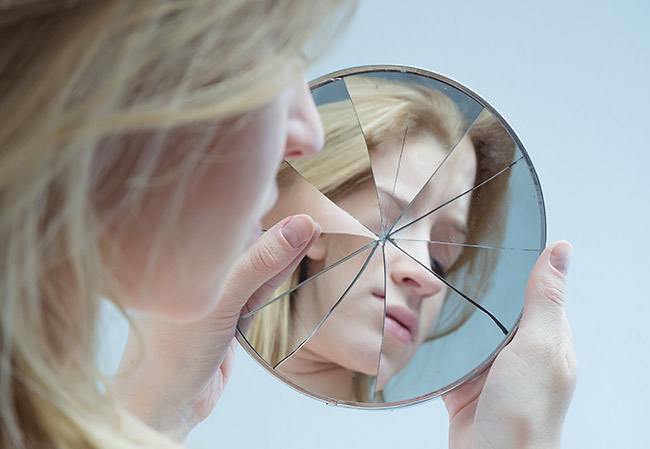 Woman not liking her image in mirror